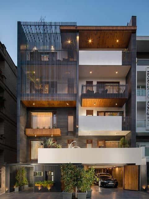 front elevation for multilevel building with jali design, tiles, and proper lighting