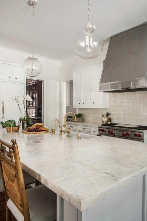 white textured quartzite countertop with wooden chairs and glass pendants.