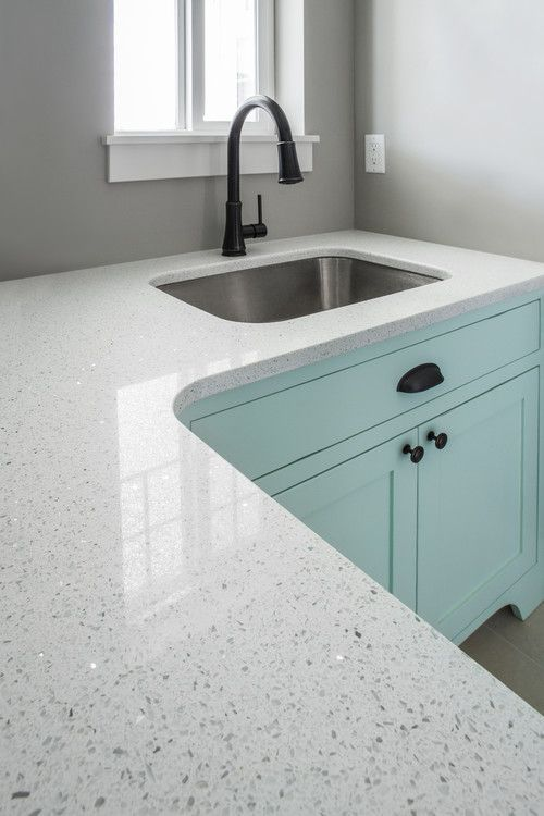 white textured quartz kitchen countertop design with light blue cabinets.