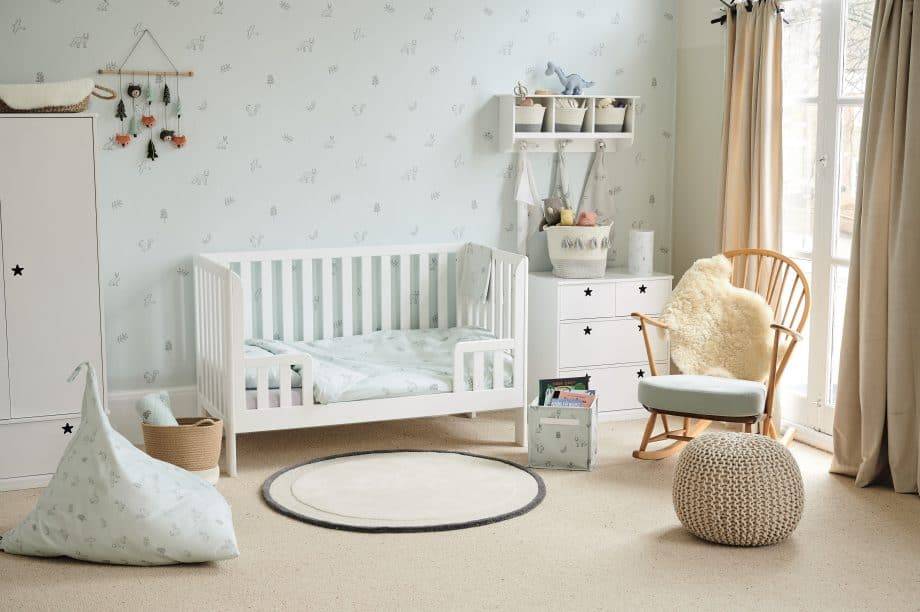 white painted cot with vertical bars on all sides