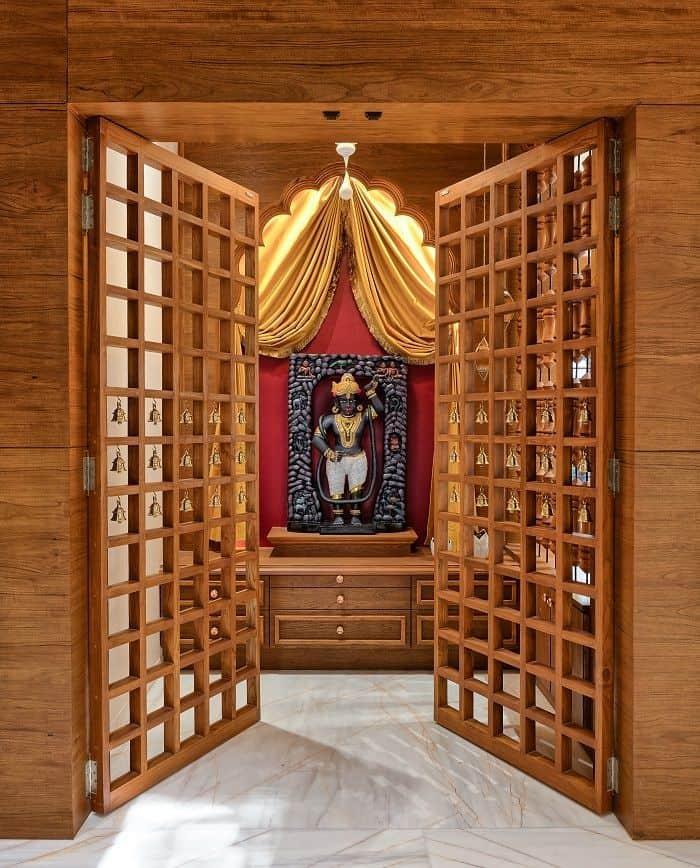 Wooden pooja room door design with golden metal embellishments