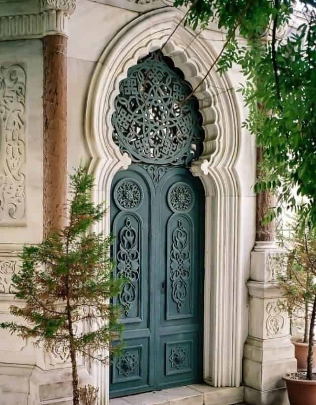 huge teal green door with carved traditional design and patterns