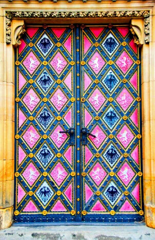 carved wooden door painted in bright pink, yellow, and blue colors