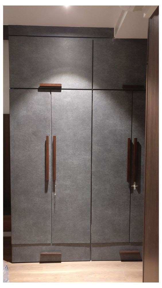 golden cylindrical handles in vertical and horizontal arrangements on a white wardrobe