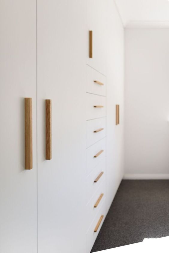 golden cylindrical handles in vertical and horizontal arrangements on a white cupboard