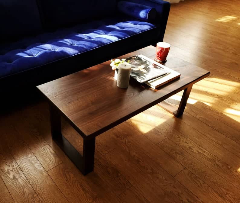 plywood coffee table with flower planter and red mug on top