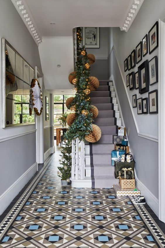 white, black, and blue mosaic flooring tiles in geometrical arrangement for entrance hallway with white and grey staircase