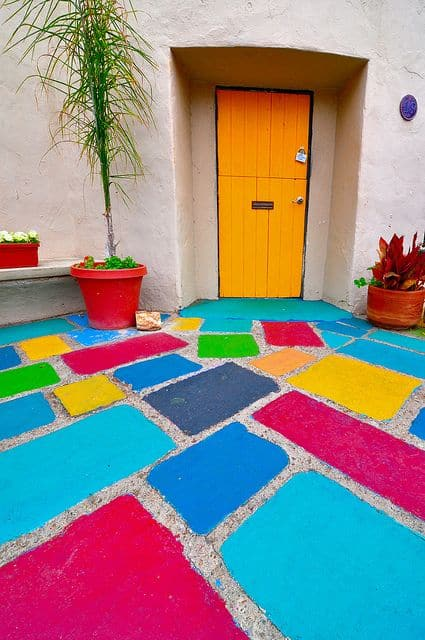 blue, pink, green, yellow floor paints for home entrance and terrace with an orange door