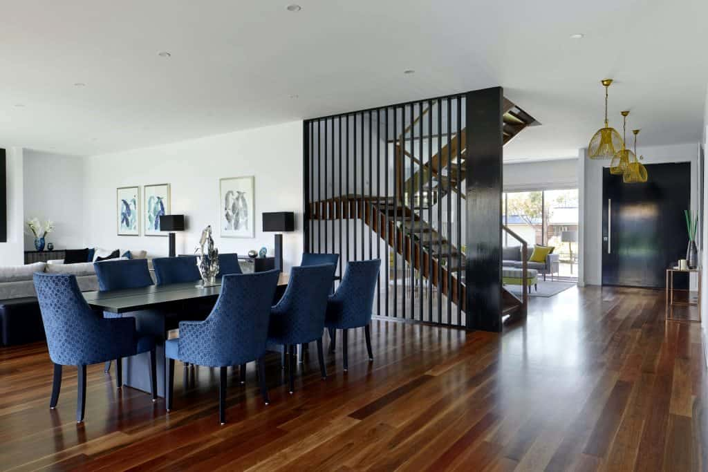 living room with dining table and blue chairs; black partition wall design and wood flooring