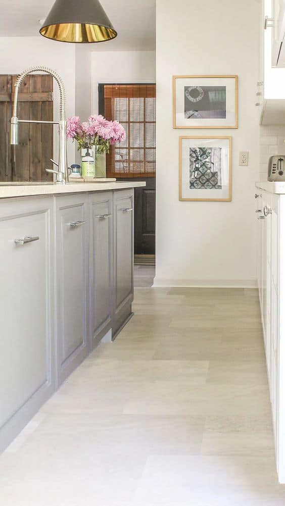 plain vinyl floor tiles in a kitchen with grey cabinets, heavy pendant light and white walls