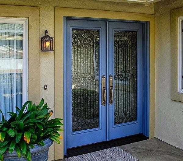 blue wooden door with a black door grill and steel handles