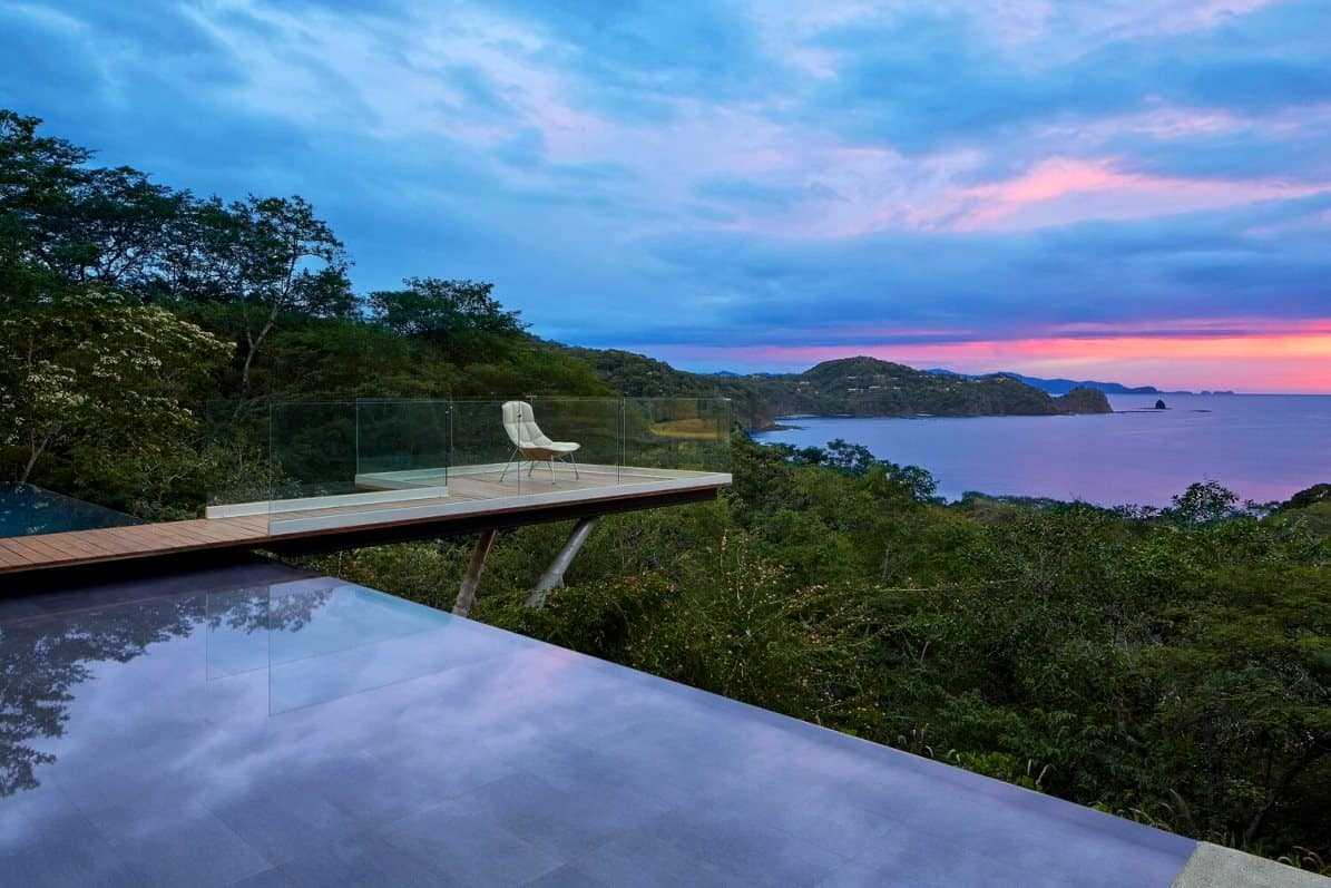 house design exterior with a scenic view of trees and the setting sun, home designs front elevation seating area on a wooden deck on a swimming pool