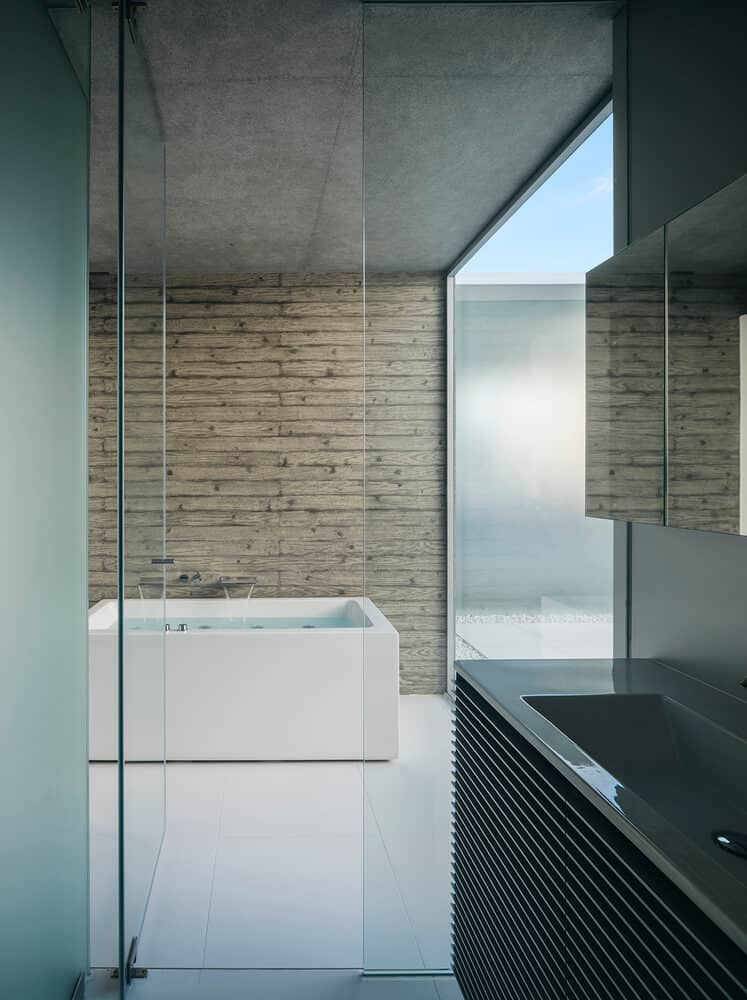 bathroom design with glass door, faux wood wall, and a white bathtub