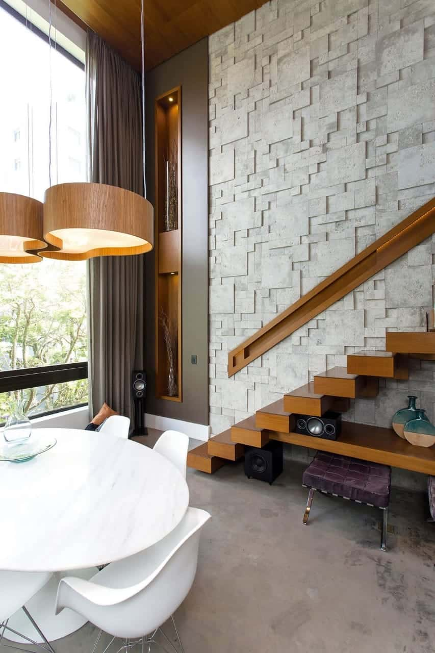 a neutral wall design with stone by the wooden stairway